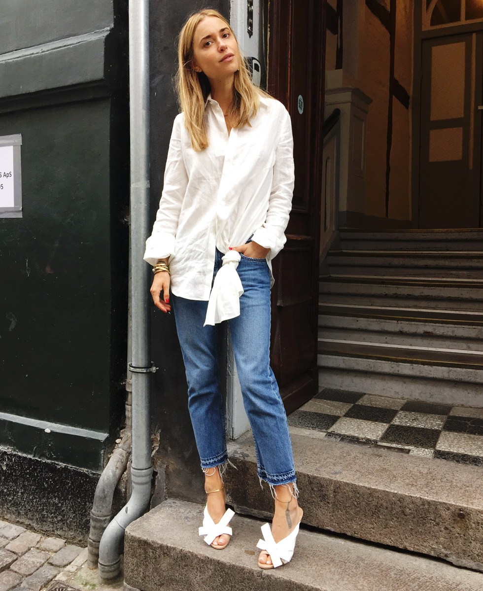 Wear the shirt backwards and tie the tails into a knot or bow. Fold the bottom of the shirt up and in to create a clean, crisp hemline. Pull the shirt around you and fasten the lower three or four buttons. Twist it around so the front lays against your side, then pull the back sleeve over the shoulder to meet the front.